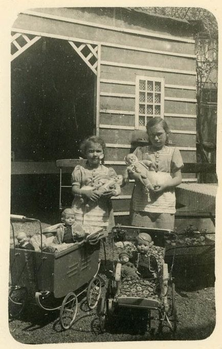 Wonderful vintage photo of two little girls and their dolls circa 1940's.