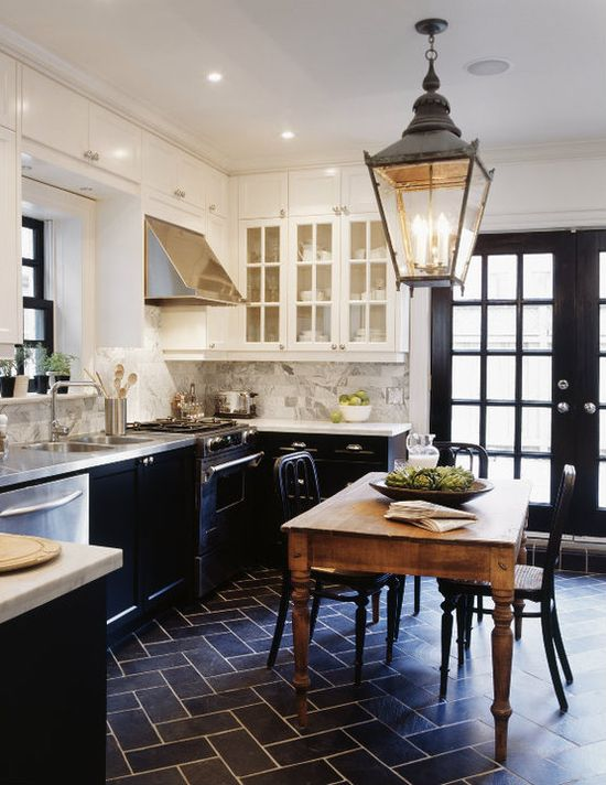 kitchens - glass-front white upper cabinets black lower cabinets black tiles floor herringbone chevron pattern white carrara marble countertops subway tiles backsplash stinless steel countertops rustic farmhouse dining table black cafe chairs glossy black French doors lantern