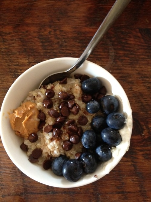 quinoa cooked in almond milk with cinnamon, coconut, carob chips, blueberries, and peanut butter