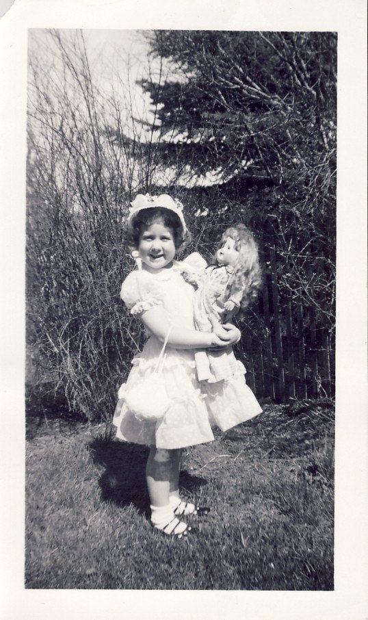 Little girl identified as Loletta Lemon, dressed in her Sunday best, holding her doll.