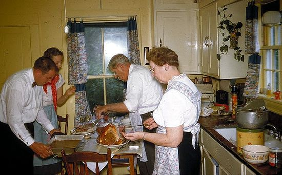 Activity abounds as a 1950s family prepares their Thanksgiving dinner in a buttery yellow hued kitchen. #kitchen #home #house #dinner #family #1950s #fifties #food #Thanksgiving #vintage