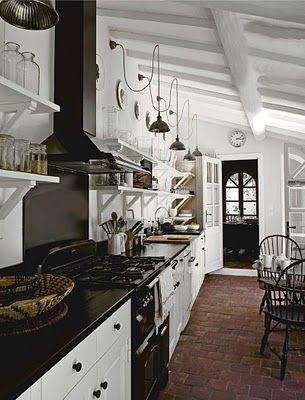Brick floors and industrial lighting in a kitchen! I like the shelving, too.