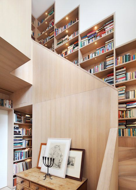 Walls of books fold around a wooden staircase in this renovation and extension to a north London home by Hackney studio Platform 5 Architects.