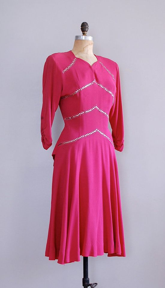 1940s dress with silver studded trim and a peplum ruffle in back.