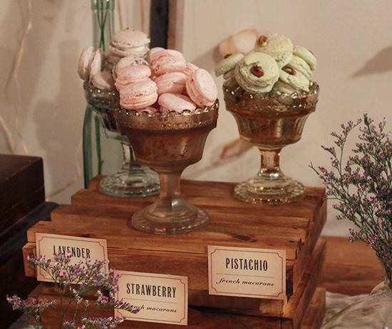 Lavendar, strawberry and pistachio macaroons are placed in antique dessert goblets and surrounded by fresh lavendar