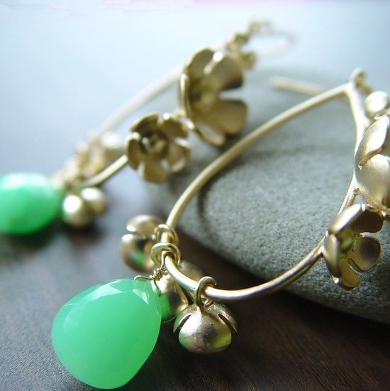 Gold drop earring with flowers and green stones.