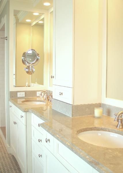 white bathroom cabinets and marble countertops.