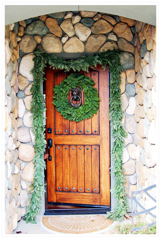 """Beautiful front door with stone surround, decorated for the holidays. {From """"Wild Ink Press"""" one of my favorite blogs for their 'before & after' pics of their own home remodel.}"""