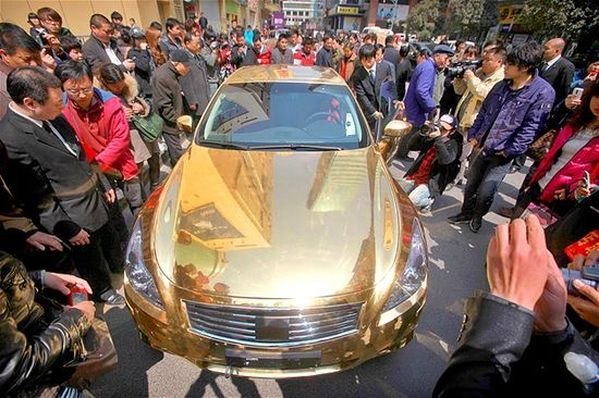 Image: A crowd gathers to admire a gold-plated Infiniti luxury sports car on display outside a jewellery store in Nanjing, China. (© AFP/Get...