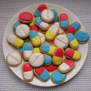 """Ha! Giant pain killers to help someone special feel better!    I wanted to make """"get well"""" cookies for someone. My cookie cutter collection is rather small so I had to come up with something using what I have. Somehow the idea of pain killer cookies came to mind.    I used a small round cookie cutter for the white pills.    The solid blue and red were made with a small oval cutter. It wasn't quite oval enough so I smooshed in the dough a bit. They're still not as oval as I would have liked. I had to hand-cut the multi-colored capsules. I used a square cutter. Sliced the dough down the middle so I had two rectangles. Then I used a knife to round the ends."""