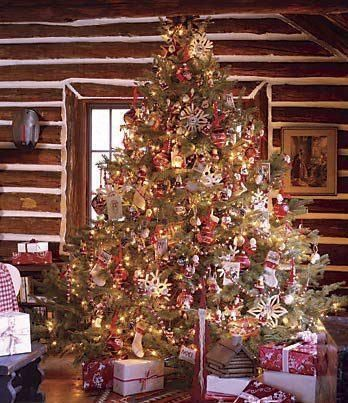 A log cabin at Christmas with a huge Christmas tree and presents