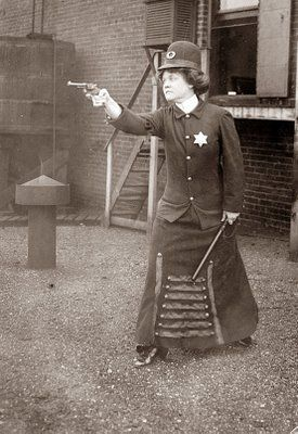 Police Woman 20's and shows a police woman with a Billy Club and packing pistol.
