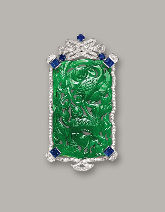 JADEITE, DIAMOND AND SAPPHIRE BROOCH, CARTIER, CIRCA 1950.   The jadeite plaque of translucent intense emerald green colour, carved with a crane & mythical beast, symbolising longevity, surmounted by a Chinese eternity knot set with circular-cut diamonds, highlighted by half moon-shaped diamonds, circular-cut sapphires and sugarloaf cabochon sapphires, the diamonds and sapphires, mounted in 18 karat white gold, signed and numbered 50-27720.