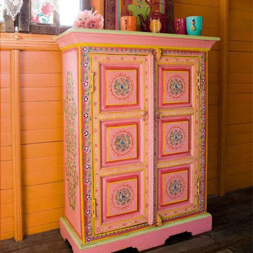 cool peachy painted cupboard in front of orangey painted walls