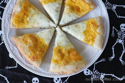 Candy Corn Pizza - What Halloween food idea could be easier that slices of a plain cheese pizza that resembles candy corn? Simply  make a ring of cheddar around the outside edge and mozzarella in the center. Cut into slices. #Halloweenfood #Halloweenparty