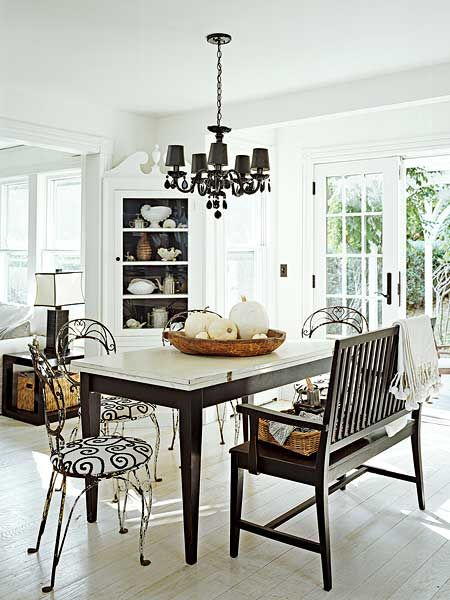 When the homeowner found the perfectly weathered set of dining chairs under a snowdrift, she immediately coated them with lacquer to preserve its natural antiquing. A black spray-painted chandelier points to a store-bought dining table topped with white milk paint and then further distressed. Whitewashed tongue-and-groove wood floors match the color of the walls and ceiling, opening up with space.