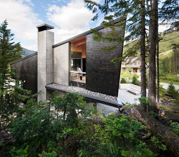 The Whistler Residence is covered partly in dark shingles, which accentuate the concrete that breaks up the form and the wood that can be seen through the large opening.