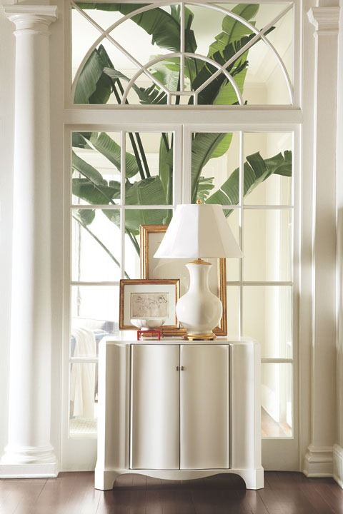 Ralph Lauren...Tropical-chic.  Love the palladian window that appears to look into another room and then you see that wonderful huge tropical plant.  Would like a different piece (or none at all) in front of the window.