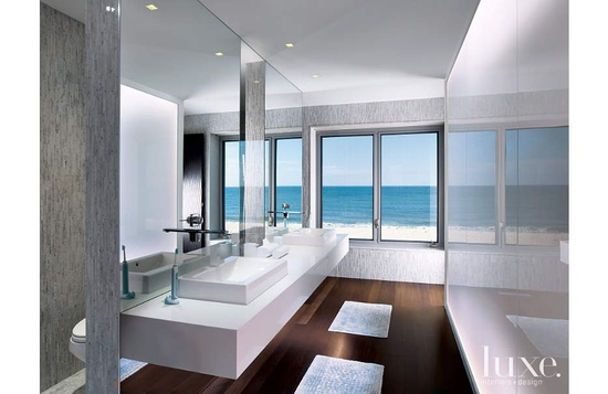 A backlit white glass wall, minimalist sinks and walls dressed in white marble shards give this master bathroom a spa-like feel.