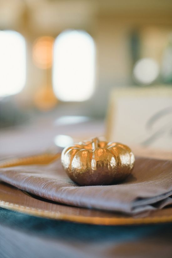 Gold pumpkins on place settings.