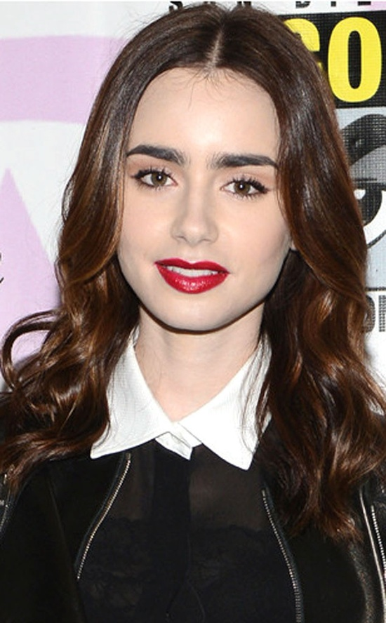 Lily Collins makes a beauty statement with glossy curls and statement red lips.