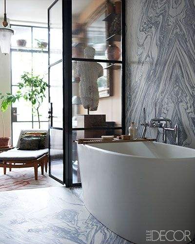 Bookended slab  ~apartment by Len Morgan The walls of the master bath are lined with cipollino marble, and the bathtub is by Wetstyle; the sculpture was purchased at Christie's, and the 1940s light fixture is by FontanaArte.