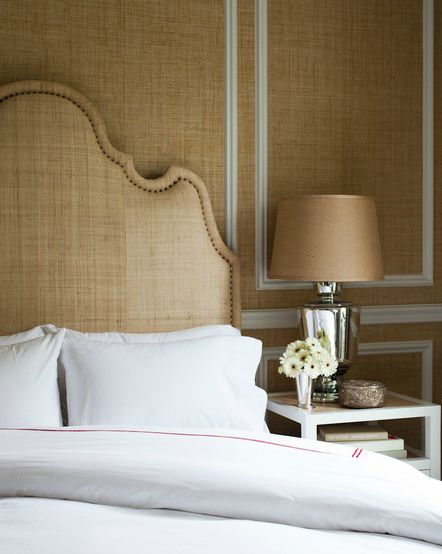 Tone-on tone luxurious bedroom with sand grasscloth wallpaper, burlap headboard with French brass tacks, mercury glass lamp with linen shade, crisp white hotel bedding with red stitching and white open nightstand.