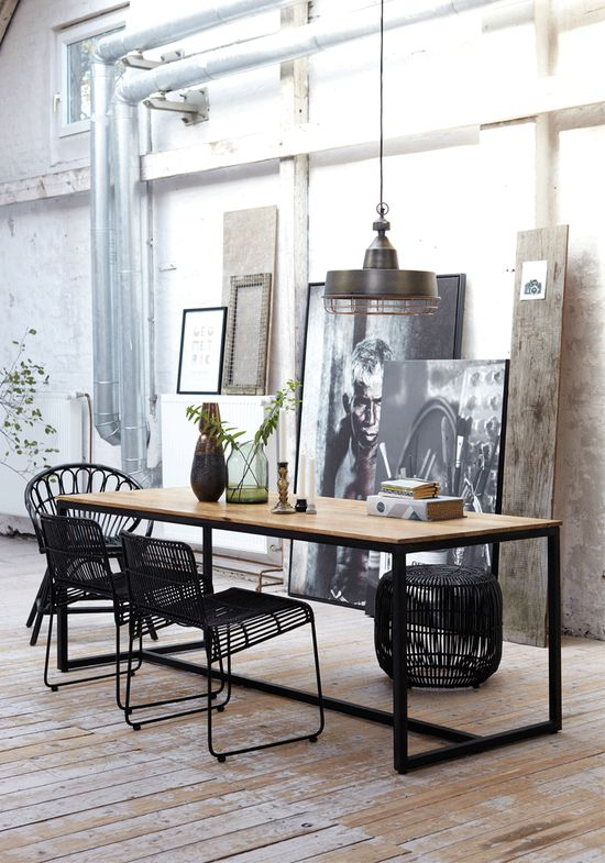 Loft with large black/white pictures on floor, wood top table and metal chairs, cool industrial pendant...very urban chic