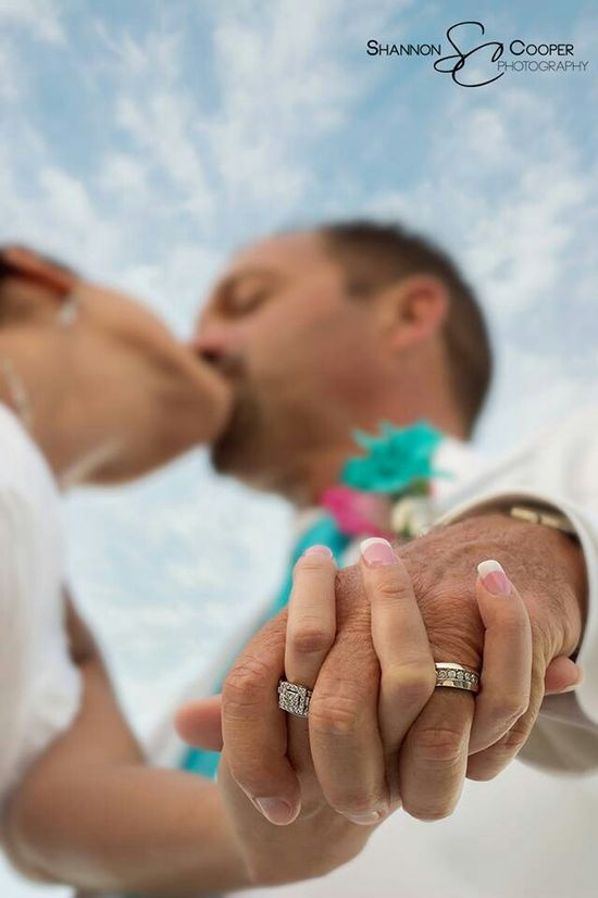 Hands down to focus on rings, kiss in background, and the blue sky and clouds!!! Great perspective and angle