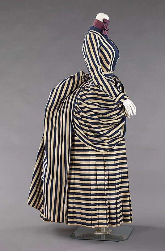 Haute Couture Victorian fashion dress gown American 1885-1888. #Historical #Costume made from cotton and silk. Printed stripe textiles were fashionable in sporting activities throughout the 19th century due to the nautical theme and their jaunty air which inspires vigor. Although the silhouette remained the same, high neckline, long sleeve with the skirt style pleated at the front and a natural flow bustle train at the back. The trimmings were reduced. #Hautecouture #Vintage #Victorian #Fashion