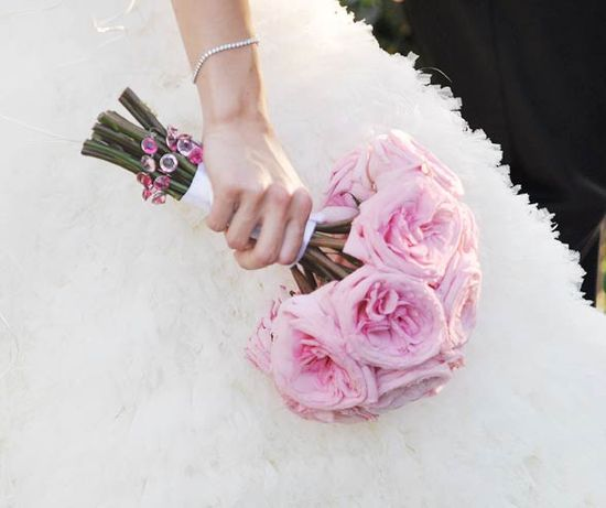 For a simple and stunning bouquet, wrap garden roses in satin ribbon and add a strand of pink crystals.