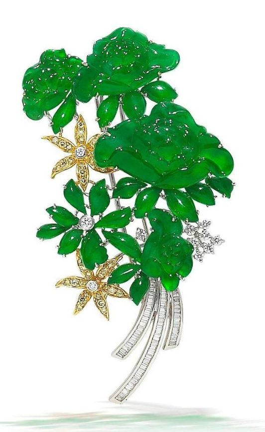 A jadeite and diamond brooch  Formed as a flower spray, set with bright apple green carved jadeite flower heads, the largest measuring approximately 18.1 x 29.7 x 2.8mm, interspersed with flowerheads set with round brilliant-cut diamonds, some of yellow hues, the stems inlaid with baguette-cut diamonds, mounted in 18k yellow and white gold, the diamonds estimated to weigh approximately 0.85 carats in total, brooch length 8.0cm