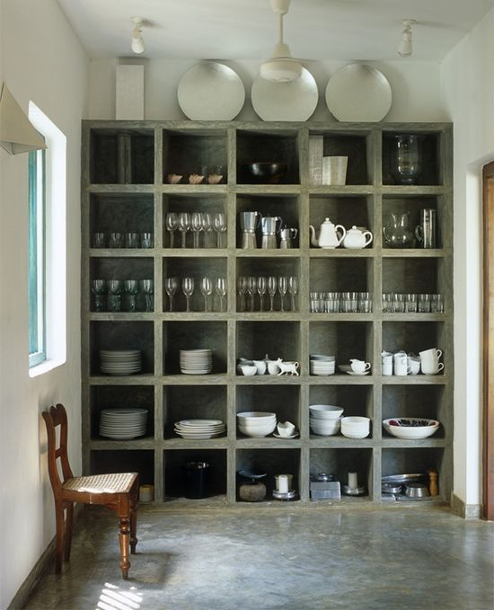 """Concrete cubbies might not be your first choice for storing porcelain, but the chunky concrete shelving unit is gorgeous. The floor in the kitchen of this house in Sri Lanka, by architect Geoffrey Bawa, is polished concrete too."""