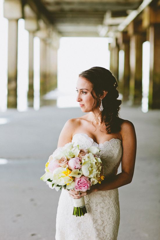 Bride in romantic lace wedding dress and pink bouquet