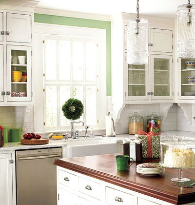 Open, Green Kitchen: Classic choices like white subway tile, vintage-style hardware, a mahogany countertop on the island, and an apron-front farmhouse sink create a no-fuss backdrop for colorful green walls in this Charlotte, North Carolina, kitchen.