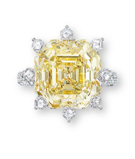 A COLOURED DIAMOND AND DIAMOND RING  Set with a rectangular-shaped fancy yellow diamond weighing approximately 15.02 carats, to the square-shaped diamond claws, brilliant-cut diamond gallery and three quarter-hoop, mounted in 18k white gold
