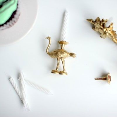 Candle holders made from plastic animal toys, spray-painted gold.