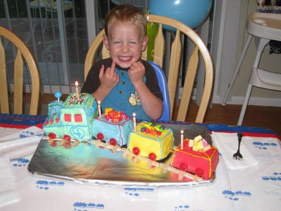 Check out this funny photo of a little boy giving the finger to the camera over his train birthday cake, on NickMom.com!