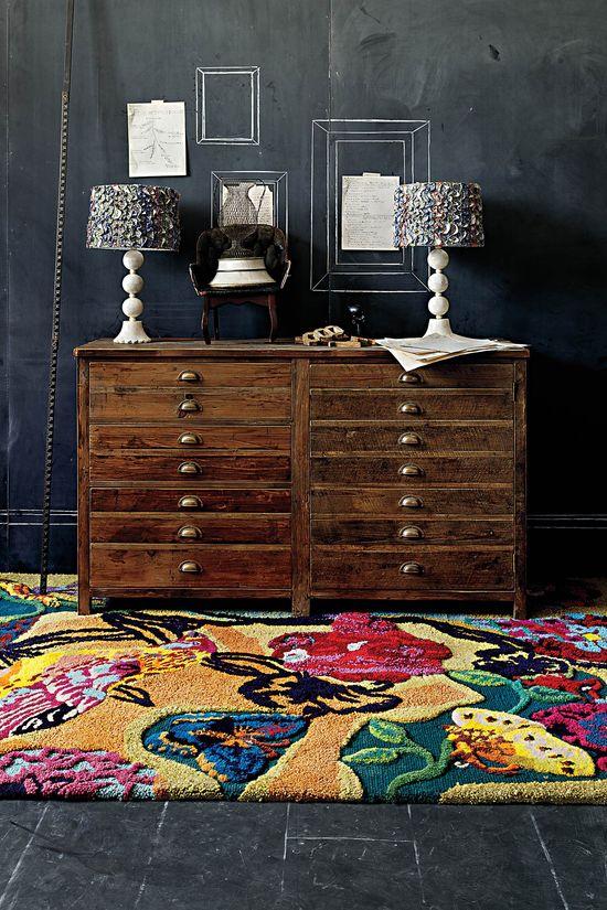 Anthropologie home decor - colorful rug, wood flat file dresser, dark walls