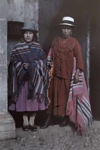 Two women pose in traditional costumes from the highlands of Peru.
