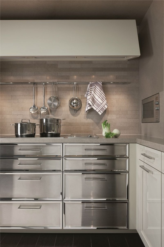 I absolutely love this design in this kitchen. I also love the play of horizontal lines found in the back splash, the hood fan, the utensil rack, cabinets and handles. Stainless steel as a decorating material offers luxury, and classic beauty. Smooth, and shiny surfaces reflect light, appear in focus, and draw the eye.