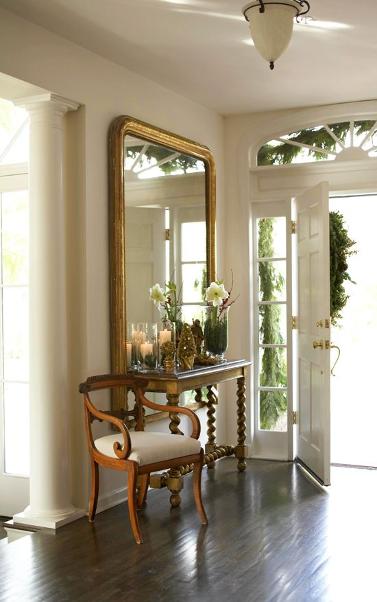 An oversized gilded mirror establishes a beautiful display in this foyer.  Traditional Home®  (The table is beautiful too.)