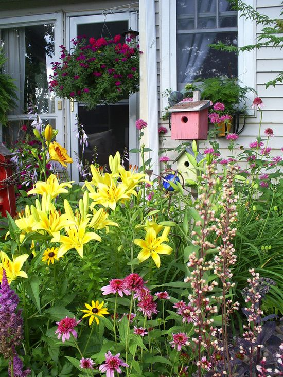 Pink double coneflower, yellow asiatic lilies. Love the birdhouse, too.