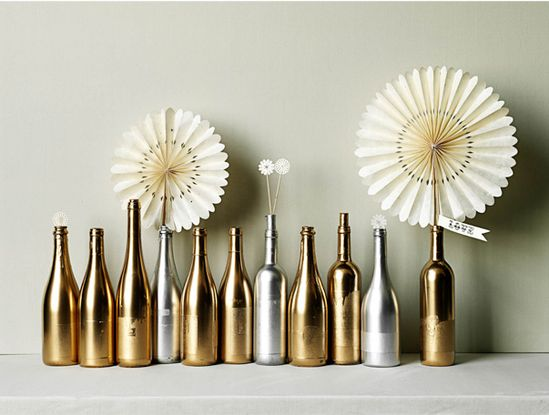 30 Minute Centerpieces - CHAMPAGNE & WINE BOTTLES make an unbelievably opulent centerpiece when massed out and sprayed entirely with gold and silver paint. Jeffrey recommends keeping the labels on (and even keeping a cork or two in a few bottles) when painting to create a 'dipped' appearance. #BHLDN #Centerpieces #Jeffery Miller #DIY
