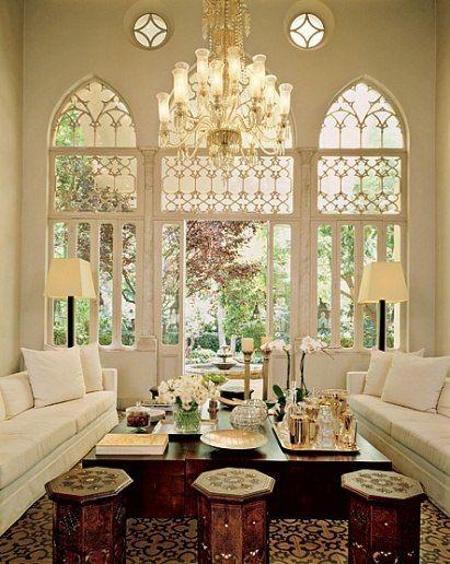 Arcos góticos en un extremo de la sala de estar dan al jardín amurallado de la propiedad.  Una antigua lámpara otomano, una de las cuatro de la casa, llama la atención hasta los techos de 20 pies de la habitación.  (La transformación de una gran residencia en la capital libanesa de Couturier ELIE SAAB)
