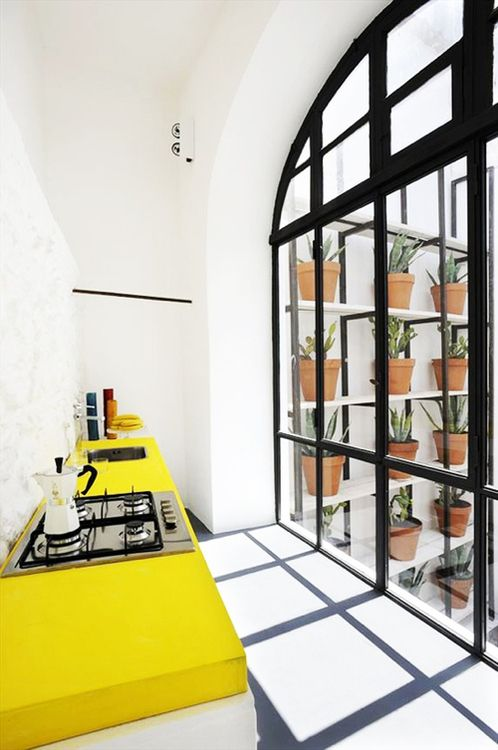 Love these black grated windows that give way to a small kitchen with a huge pop of color