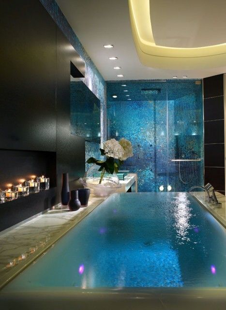 This is a STUNNING, infinity bathtub with led color changing lights inside. The tub is surrounded by marble and there is a unique wall covering in black. The bathtub looks like a small pool! The shower is gorgeous as well with iridescent blue tiles shimmering in the background. This truly is a luxurious bathroom!