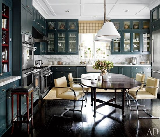 A Houston Home Gets an Ultra-Refined Makeover, J Randall Powers redo of his 1990s Houston home, Knoll's Brno chairs surround an antique table in the kitchen, where Powers paneled the ceiling and installed cabinets whose rich gray-green hue gives the space a sense of intimacy; Neolithic Chinese pottery is displayed at the top of the upper cabinets, and the hood, ovens, and range are by Thermador.