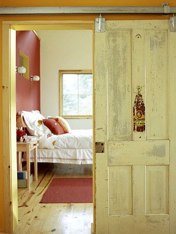 This vintage door was mounted on a track like a barn door. More ways to decorate with vintage finds: www.bhg.com/...  I've seen this idea a few times.  I think my house is set up perfect for this and I want to try a door like this.