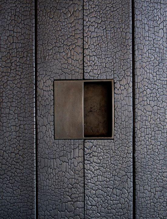 Burned wood + brass door handle detail